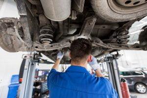 mechanic man or smith repairing car at workshop PLNY9CQ